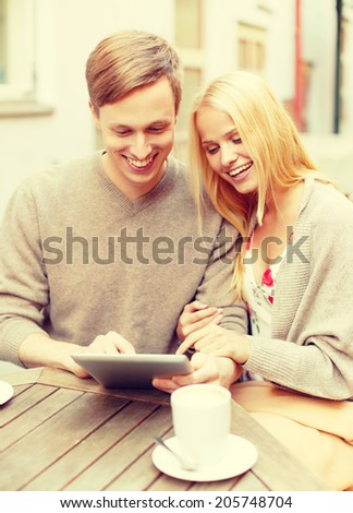 summer holidays, dating and technology concept - couple looking at tablet pc in cafe in the city - stock photo