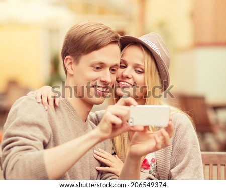 summer holidays, dating and technology concept - couple taking selfie with smartphone at cafe in the city