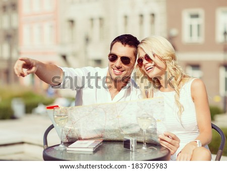 summer holidays, dating and tourism concept - couple with map in cafe in the city