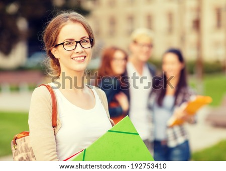 summer holidays, education, campus and teenage concept - smiling female student in black eyeglasses with folders and group in the back - stock photo