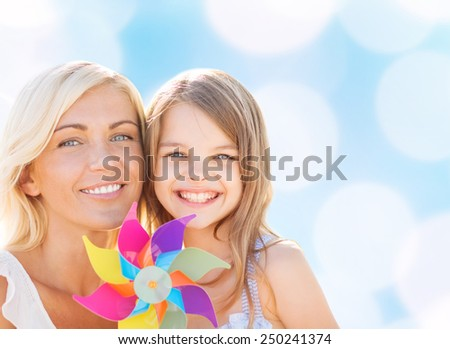 summer holidays, family, children and people concept - happy mother and girl with pinwheel toy over blue lights background - stock photo
