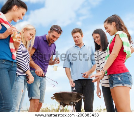 summer holidays, food and drink, happy people concept - group of friends making barbecue on the beach - stock photo