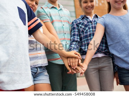 summer holidays, friendship, childhood, leisure and people concept - group of happy pre-teen kids putting hands together