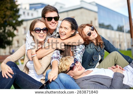 summer holidays, friendship, leisure and teenage concept - group of students or teenagers hanging out and hugging at campus or park - stock photo