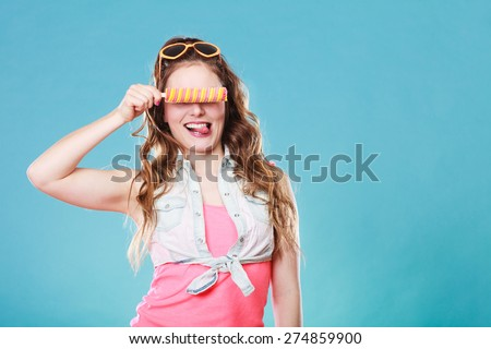 Summer holidays happiness concept. Happy joyful and cheerful young woman female model covering eyes with popsicle ice pop on blue background