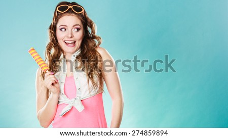 Summer holidays happiness concept. Happy joyful and cheerful young woman female model eating popsicle ice pop on blue background - stock photo