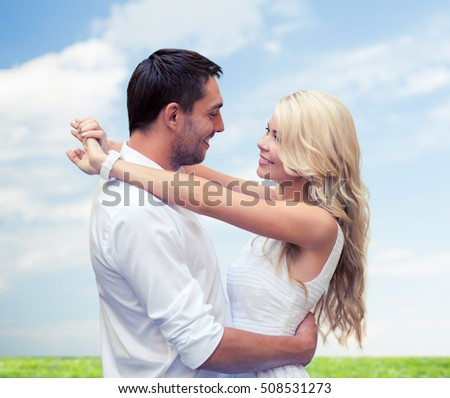 summer holidays, people, love and dating concept - happy couple hugging over blue sky and grass background