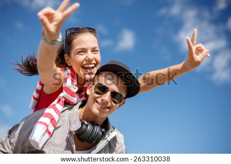 summer holidays, relationships and teenage concept - smiling teenagers in sunglasses having fun outside and showing v-sign - stock photo