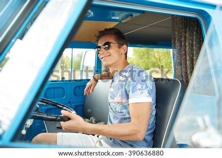 summer holidays, road trip, vacation, travel and people concept - smiling young hippie man driving in minivan car - stock photo