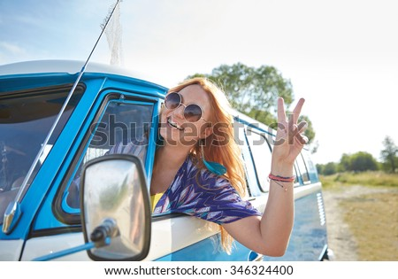 summer holidays, road trip, vacation, travel and people concept - smiling young hippie woman driving minivan car and showing peace gesture - stock photo