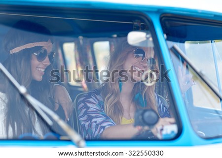 summer holidays, road trip, vacation, travel and people concept - smiling young hippie women driving minivan car and showing peace gesture - stock photo