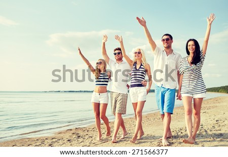 summer, holidays, sea, tourism and people concept - group of smiling friends in sunglasses walking on beach and waving hands