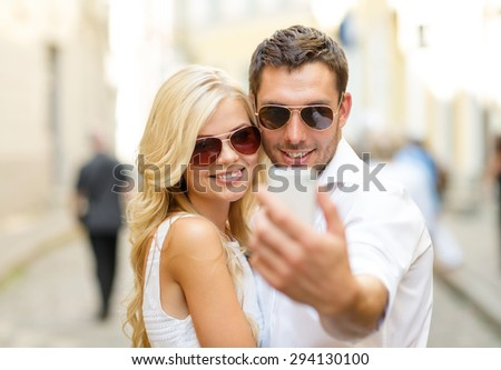 summer holidays, technology, love, relationship and dating concept - smiling couple taking picture with smartphone in the city