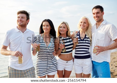 summer, holidays, tourism, drinks and people concept - group of smiling friends with bottles drinking beer or cider on beach - stock photo