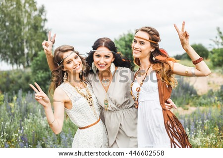 Summer holidays, travel and people concept -Three beautiful cheerful hippie girls, best friends, trendy hairstyles, feathers in her hair, white dress, tattoo flash, accessories, Bohemian, Bo-ho Style - stock photo