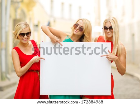 summer holidays, , travel, tourism and advertisement concept - three happy blonde women with blank white board in the city - stock photo