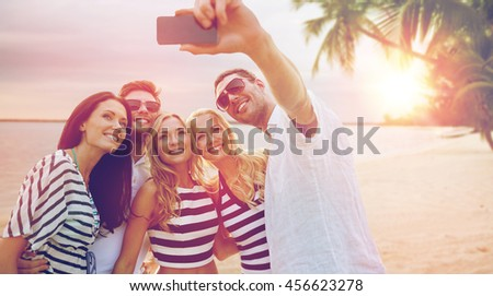 summer holidays, travel, tourism, technology and people concept - group of smiling friends with smartphone photographing and taking selfie over exotic tropical beach background - stock photo