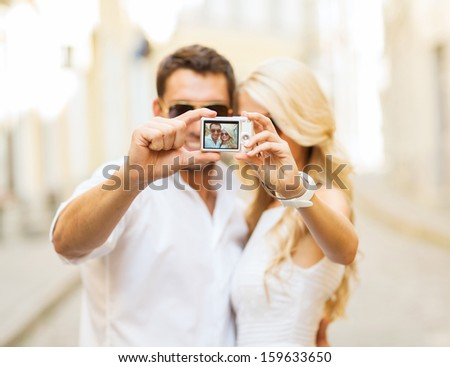 summer holidays, travel, vacation, tourism and dating concept - travelling couple taking selfie with digital camera - stock photo
