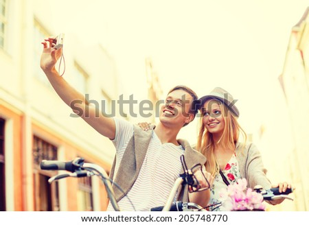 summer holidays, travel, vacation, tourism and dating concept - travelling couple with bicycles taking photo picture with camera - stock photo
