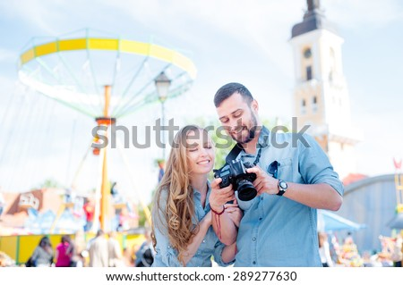 summer holidays, traveling and dating concept - smiling young couple with photo camera in the city - stock photo
