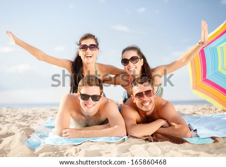 summer, holidays, vacation and happy people concept - group of smiling people in sunglasses having fun on the beach - stock photo