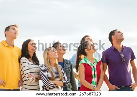 summer holidays, vacation and people concept - group of happy friends looking up on beach - stock photo