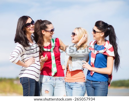 summer holidays, vacation and people concept - happy teenage girls in sunglasses or young women talking on beach - stock photo