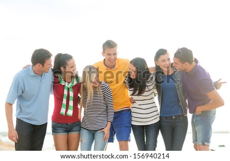 summer, holidays, vacation, happy people concept - group of friends having fun on the beach - stock photo
