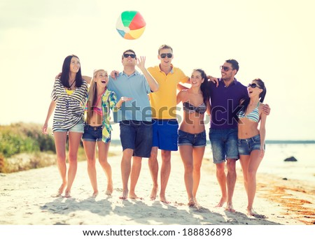 summer, holidays, vacation, happy people concept - group of friends having fun with ball on the beach - stock photo