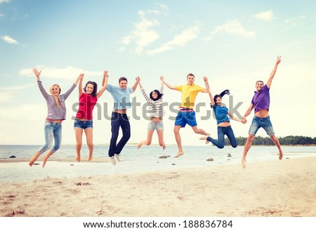 summer, holidays, vacation, happy people concept - group of friends jumping on the beach - stock photo