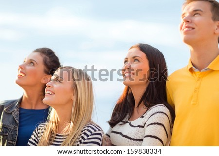 summer, holidays, vacation, happy people concept - group of friends looking up on the beach