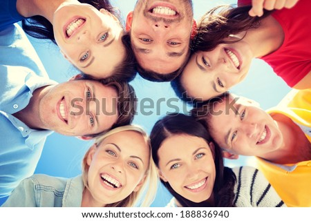 summer, holidays, vacation, happy people concept - group of teenagers looking down - stock photo