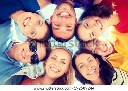 summer, holidays, vacation, happy people concept - group of teenagers looking down