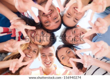 summer, holidays, vacation, happy people concept - group of teenagers looking down and showing finger five gesture - stock photo