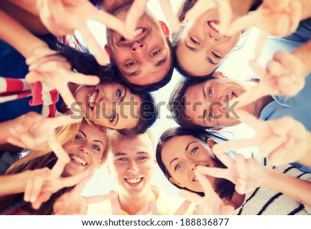 summer, holidays, vacation, happy people concept - group of teenagers looking down and showing finger five gesture