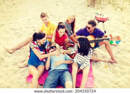 summer holidays, vacation, music, happy people concept - group of happy friends having picnic and playing guitar on beach, drinking non-alcoholic beer or soda lemonade - stock photo