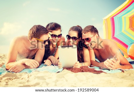 summer, holidays, vacation, technology and happy people concept - group of smiling people in sunglasses with tablet pc on the beach - stock photo