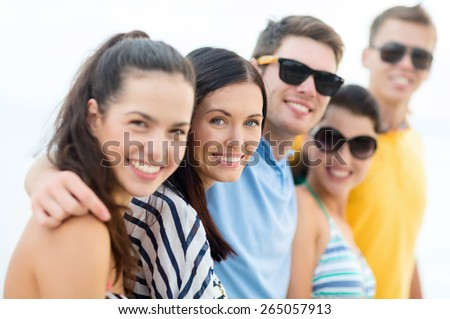 summer holidays, vacation, tourism, travel and people concept - group of happy friends hugging on beach