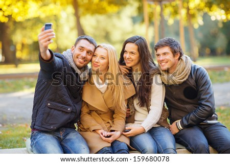 summer, holidays, vacation, travel and tourism concept - group of friends or couples having fun with smartphone photo camera in autumn park