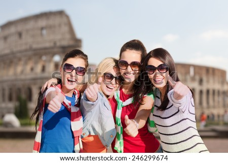 summer holidays, vacation, travel, friendship and people concept - happy teenage girls or young women in sunglasses showing thumbs up and laughing over coliseum background - stock photo