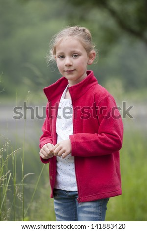 summer holidays: young girl in red outdoors in nature - stock photo