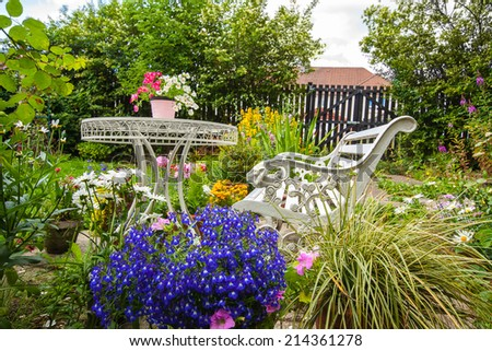 Summer home garden with white bench and a table - stock photo