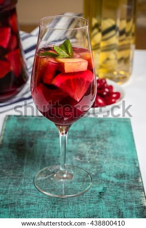 Summer home wine with fruits, sangria cocktail, in wine glass, fresh dogwood berries plate, bright blue background, food photo - stock photo