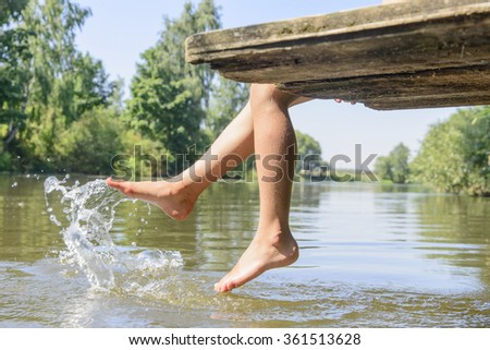 Summer hot day. The girl on the bridge, feet on water podymat splashes - stock photo