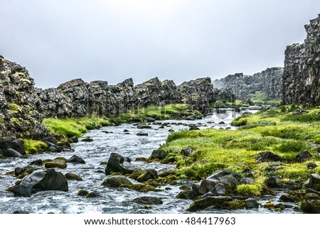 Summer Iceland landscape with river, sharp stones and grass