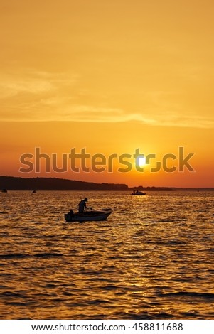 Summer in Croatia. Fisherman in his boat at sunset.