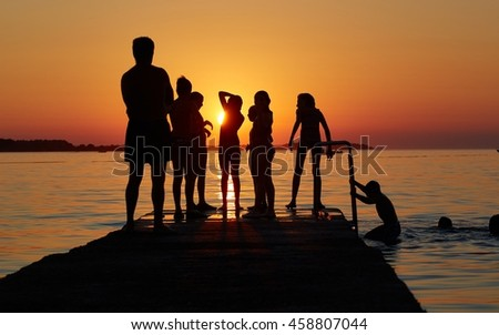 Summer in Croatia. Silhouettes of kids having fun on the pier at sunset - Playing, swimming and jumping in the water.