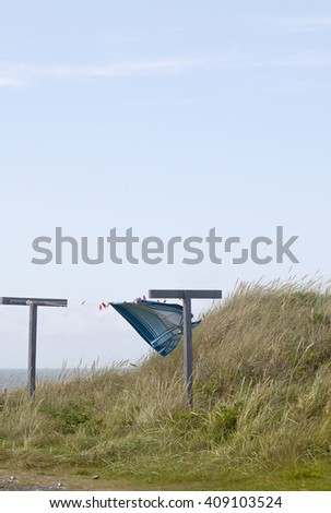Summer in Denmark. Summer in Denmark means summer houses, sea, blue skies and wind. A beach towel dances in the wind on an old washing line surrounded by sand dunes, dune grasses and a big blue sky. - stock photo