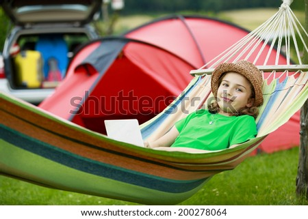 Summer in the tent - young girl with family on the camping - stock photo