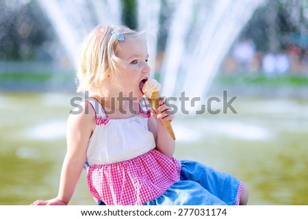 Summer in town. Happy child enjoying hot day outdoors. Cute little toddler girl eating ice cream outdoors in city park. Beautiful blurred fountain at background. - stock photo